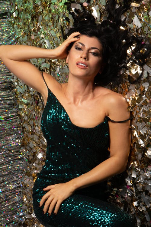 Gorgeous woman in festive dress lying on confetti