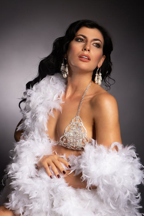 Sensual female with makeup in underwear and feather boa showing bare skin and looking away