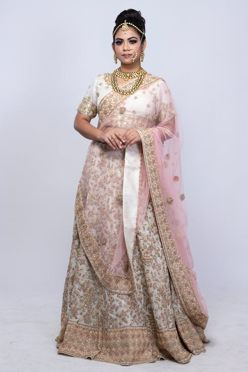 Full body of Indian female wearing traditional authentic wedding dress and precious accessories standing against gray background