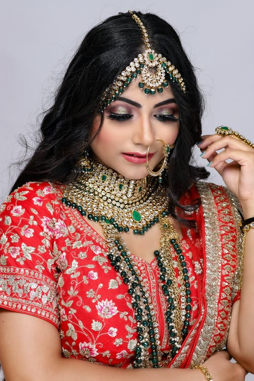Young Indian female wearing traditional authentic Indian dress and nathi ring and jewelry on neck and head