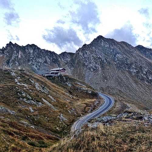 Gray Asphalt Road Near A Rocky Mountain Under White Cloudy Sky