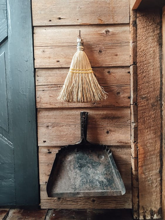 Straw broom and shovel hanging on wooden wall