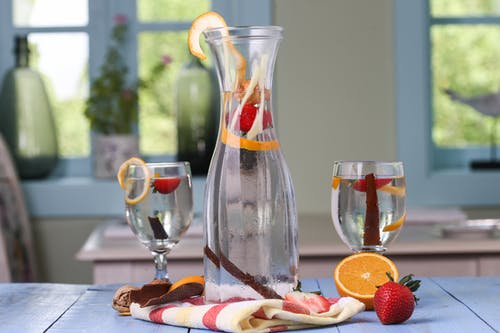 Detox Drink In Clear Glass Pitcher With Sliced Orange Fruit and Strawberry