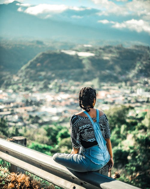 Woman in Blue Denim Vest Sitting on Brown Wooden Railings