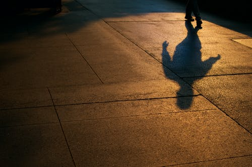 Person Walking on Gray Concrete Pavement during Night Time