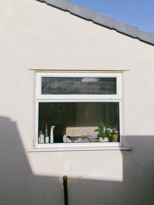 Opened window of white rural cottage