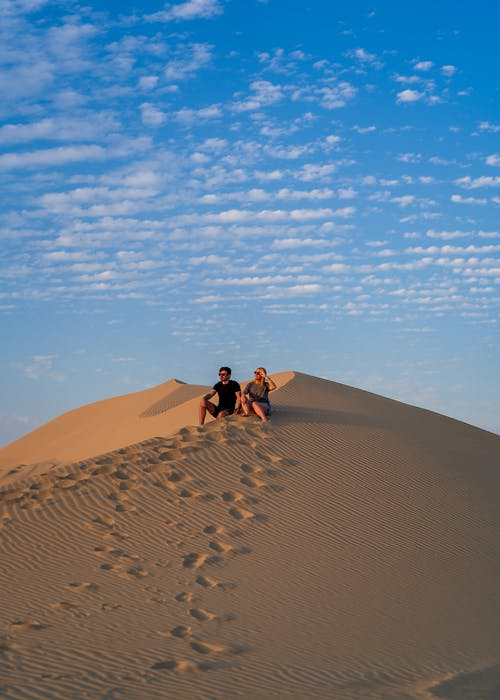 Unrecognizable traveling couple sitting on tall sandy dune and admiring nature during trip in desert on sunny day