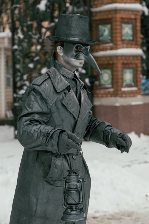 Unrecognizable person in mask and costume of plague doctor standing on street in winter