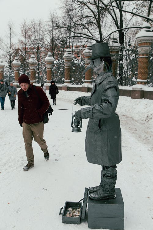 Anonymous person in costume of statue of plague doctor standing in snowy park while working outdoors