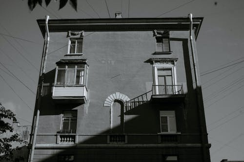 Black and white of exterior of old dwell building with balconies and ornamental windows under sunlight