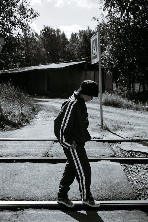 Anonymous man walking on railways in city