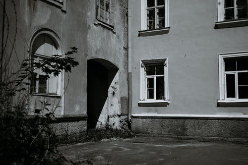 Black and white of old house with classic architecture and weathered walls on street