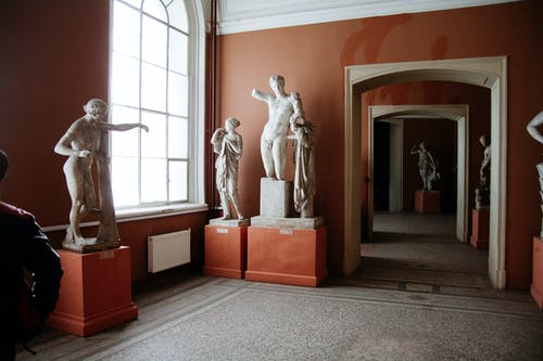 Interior of old museum with various sculptures of famous people and arched passage