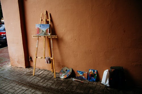 Timber easel placed with picture of pastel colors near wall with palette with paint