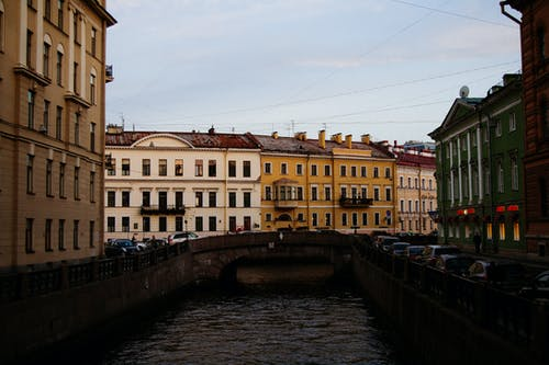 Granite embankment of canal between historical residential buildings and old bridge located in center of Saint Petersburg on cloudy day in Russia