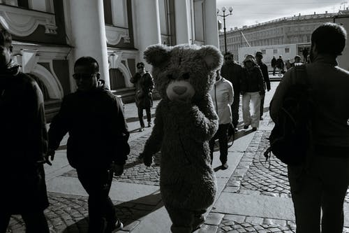 Black and white of tourists and actor dresses as bear  walking near Winter palace in Saint Petersburg Russia on sunny day