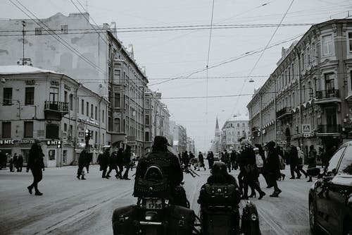 Black and white of people crossing asphalt road while cars and motorcycle with sidecar waiting for permission signal of traffic light in city in daylight