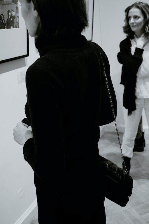 Crop stylish women in art exhibition in gallery