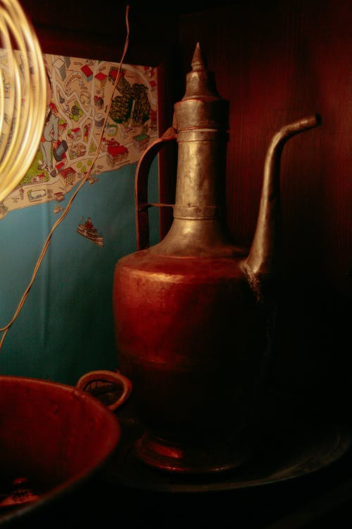 Aged jug with thin handle and nose near metal bowl and ornamental wall in house