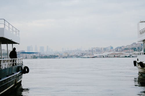 Back view of anonymous male admiring town from nautical transport on lake under cloudy sky in port