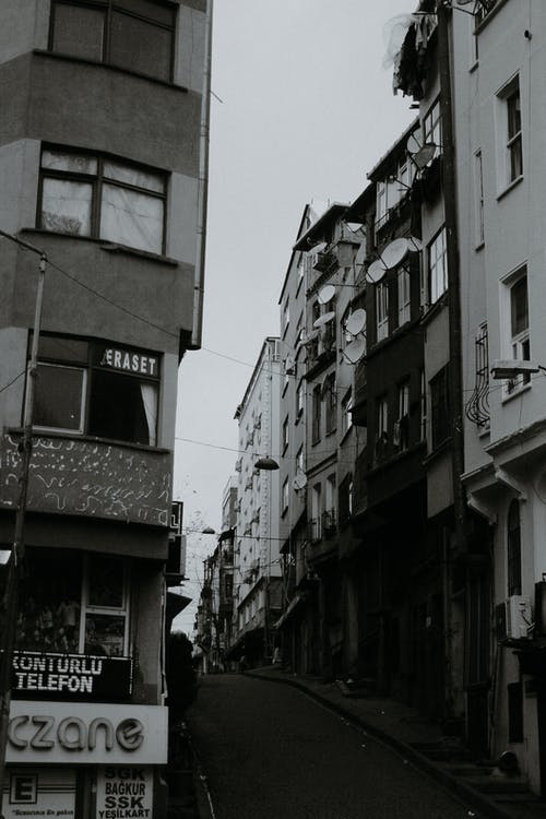 Black and white of aged multistory dwelling building exteriors with inscriptions in city in daytime