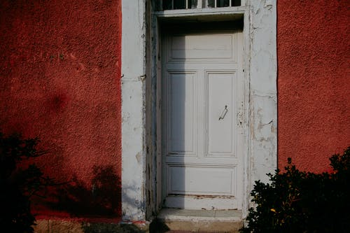 Entrance door of old building with red stucco