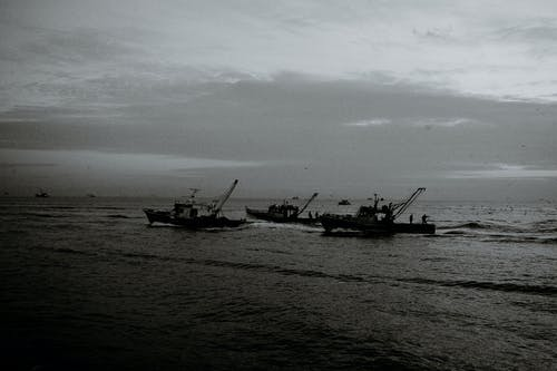 Black and white of unrecognizable fishermen on trawling boats with fishing nets on rippled ocean under cloudy sky
