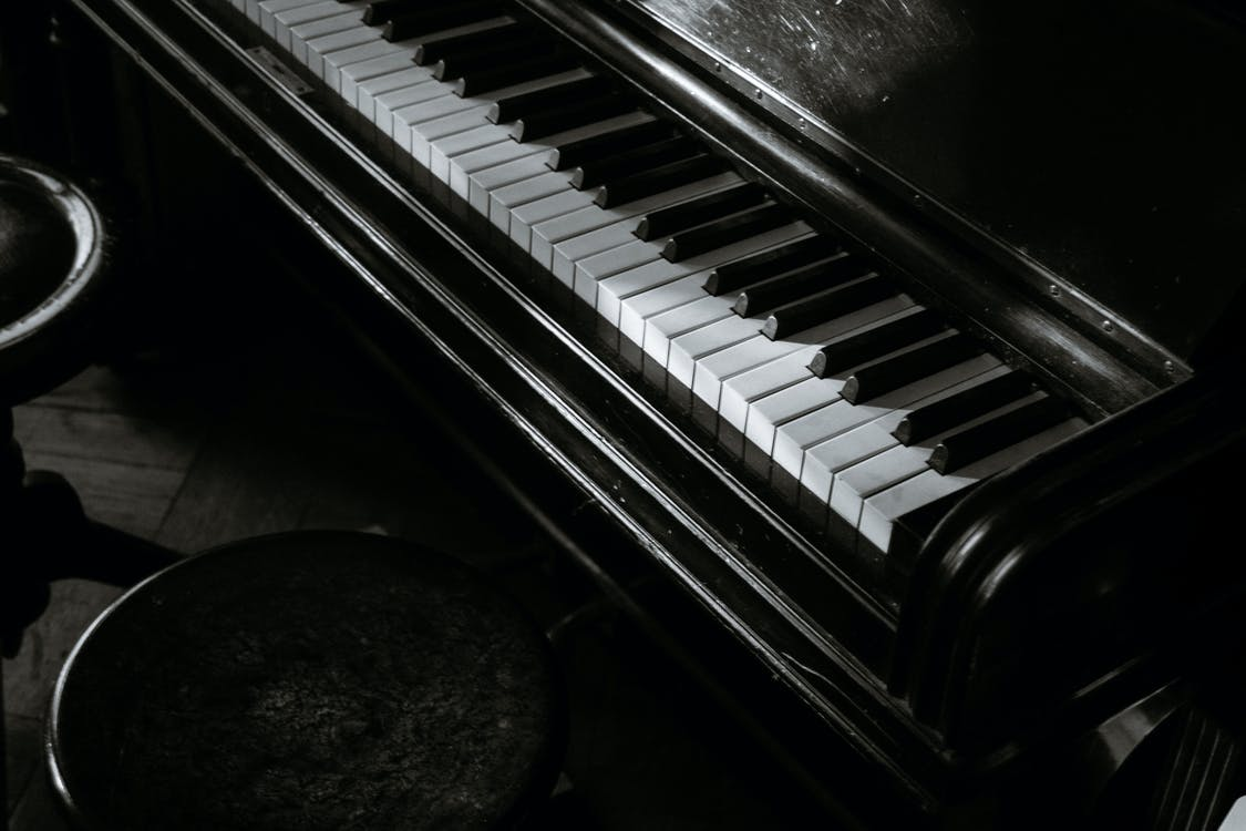 Black and white of aged piano with open keyboard near round shaped stools in building