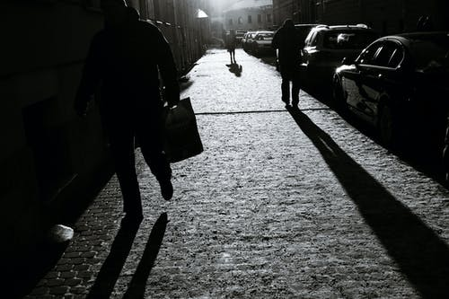 Black and white of crop unrecognizable people walking on cobblestone walkway with shadows in town in sunlight