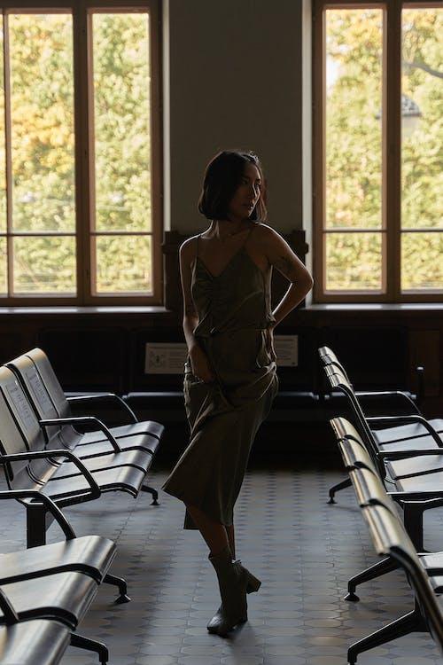 창 근처에 서 갈색 민소매 드레스 여자