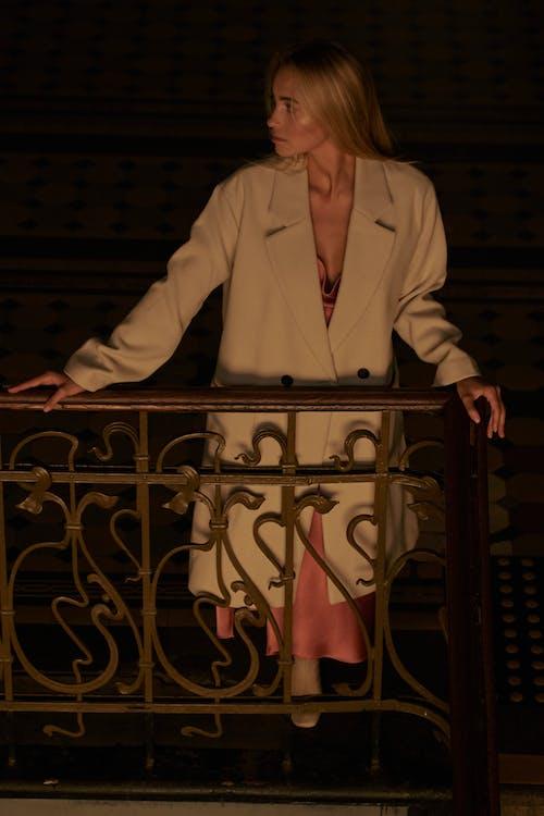 갈색 나무 울타리 옆에 서있는 흰색 재킷에 여자
