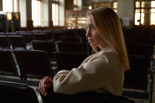 흰색 긴 소매 셔츠 블랙의 자에 앉아있는 여자