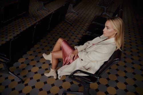 黒い椅子に座っている白い長袖シャツの女性