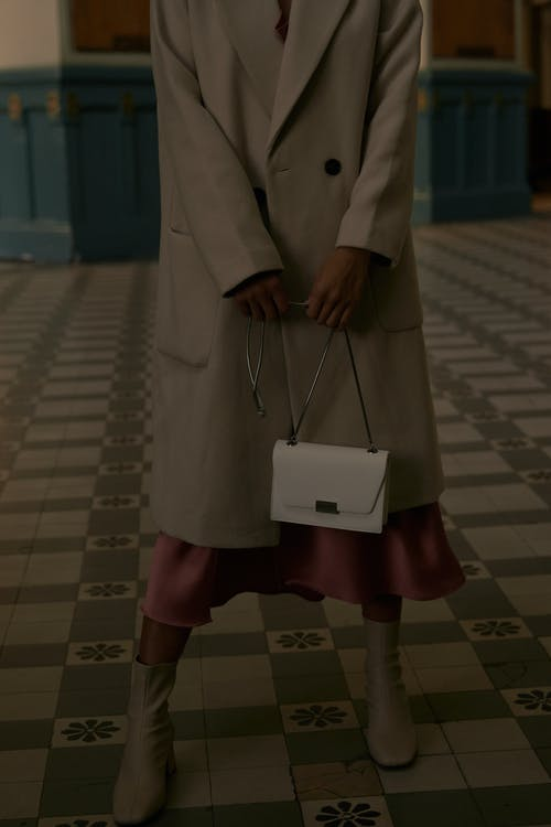 Woman in Brown Coat Holding White Paper Bag