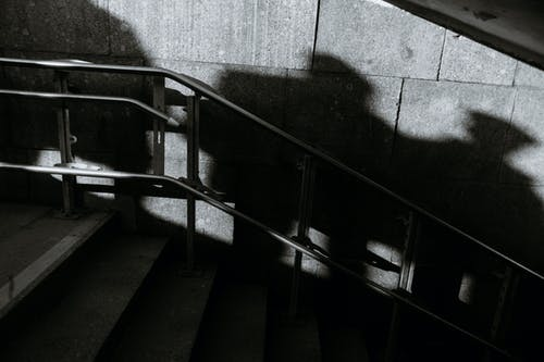 Urban staircase with railing near wall with unrecognizable people shades