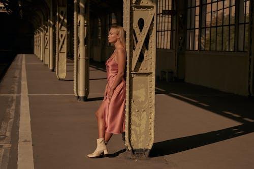 Женщина в красном платье стоит на сером бетонном полу