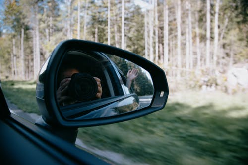 Faceless woman taking photo through car mirror