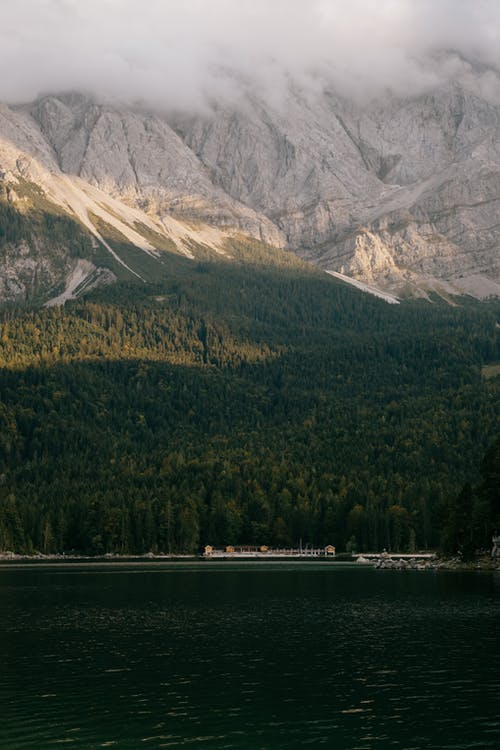 Tranquil remote lake with buildings on shore against lush greenery under rocky mountains