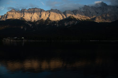 Peaceful lake with woods on shore and mountains illuminated with rays of sunset light