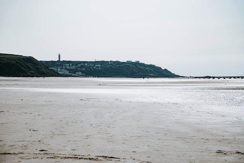 Calm empty seashore with small town