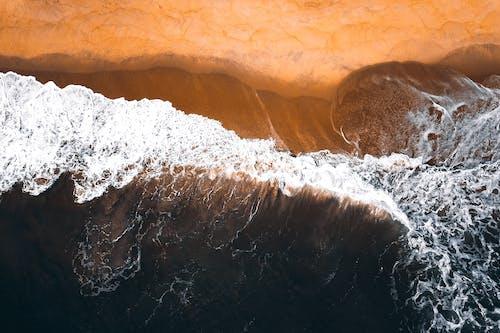 Stormy waves of ocean washing sandy coastline