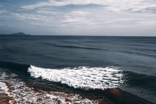 Waves of stormy endless ocean under cloudy sky