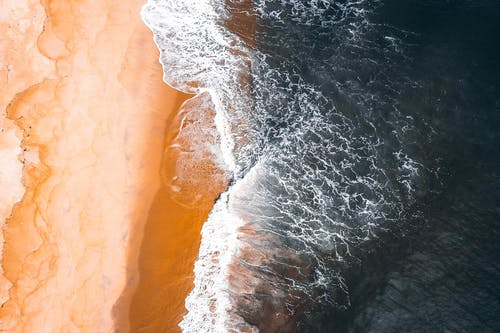 Aerial view of wavy ocean rolling on sandy beach in tropical country in daylight