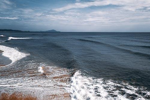 Blue ocean waves washing sandy shore