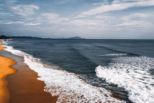 Picturesque view of foamy ocean waves washing sandy wet coast under blue sky