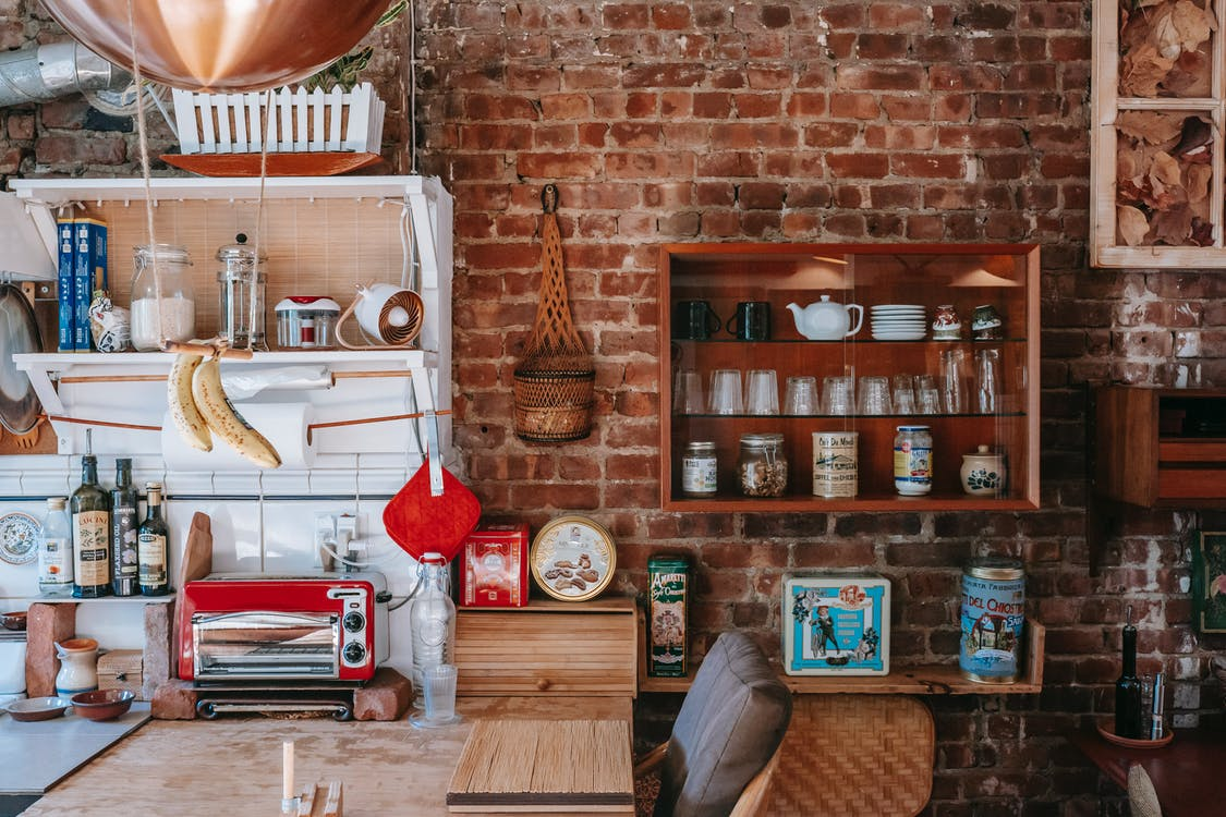 Vintage interior design with many cupboards filled with various dishware and decorations against shabby brick wall