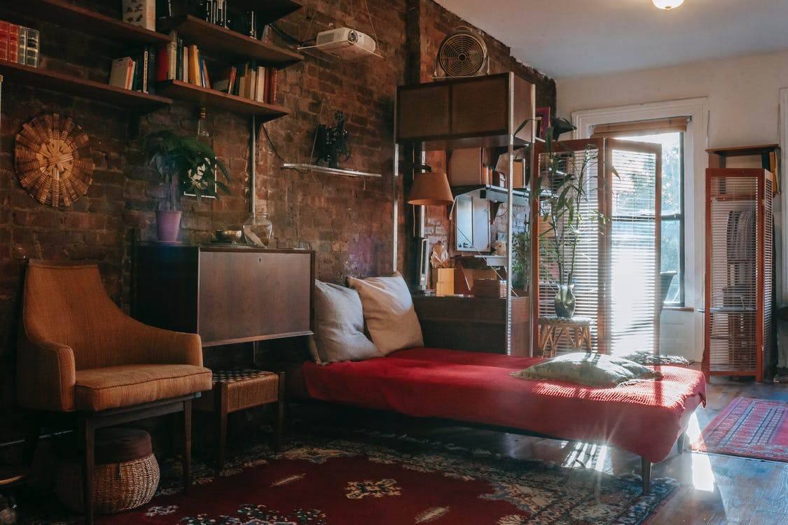 Vintage styled bedroom interior with classic wooden furniture and bookshelves decorated weathered brick wall near comfortable bed and armchair