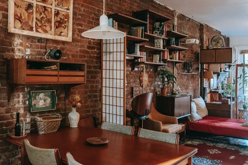 Dining zone and bed in stylish flat with brick walls