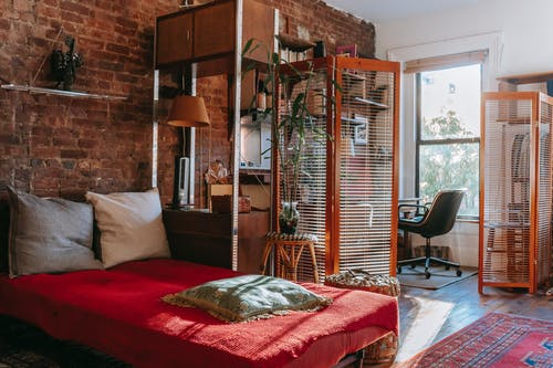 Comfortable bed with red cover and pillows placed near brick wall in cozy room with isolated workspace decorated with houseplants near window