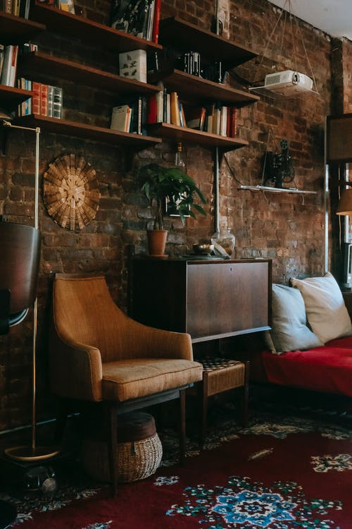 Interior details of cozy apartment with wooden cabinet and comfortable armchair placed near brick wall decorated with bookshelves and potted plant